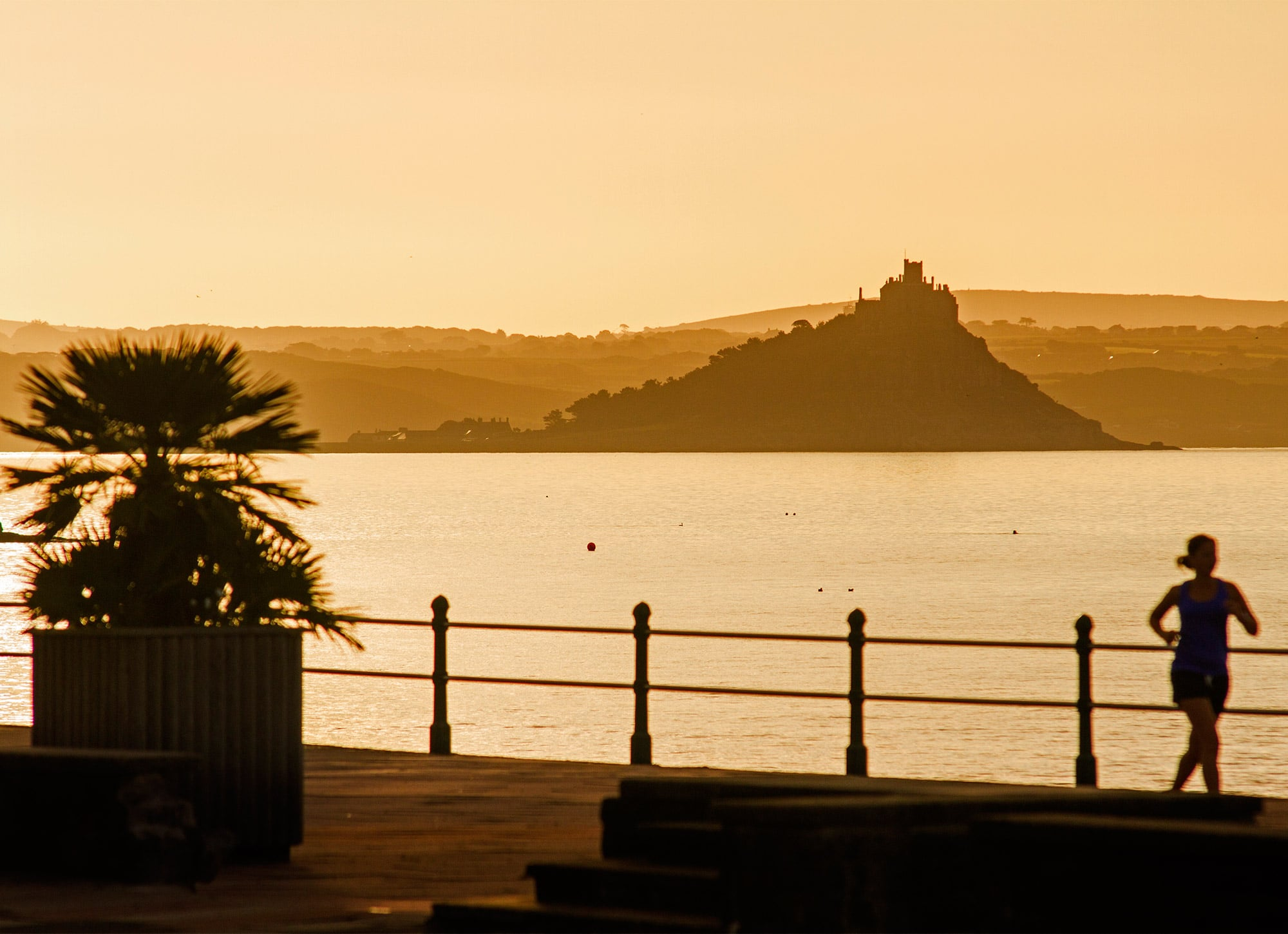 Silhouette of a jogger running along the Penzance promenade at sunset with St Michael's mount a misty silhouette on the horizon