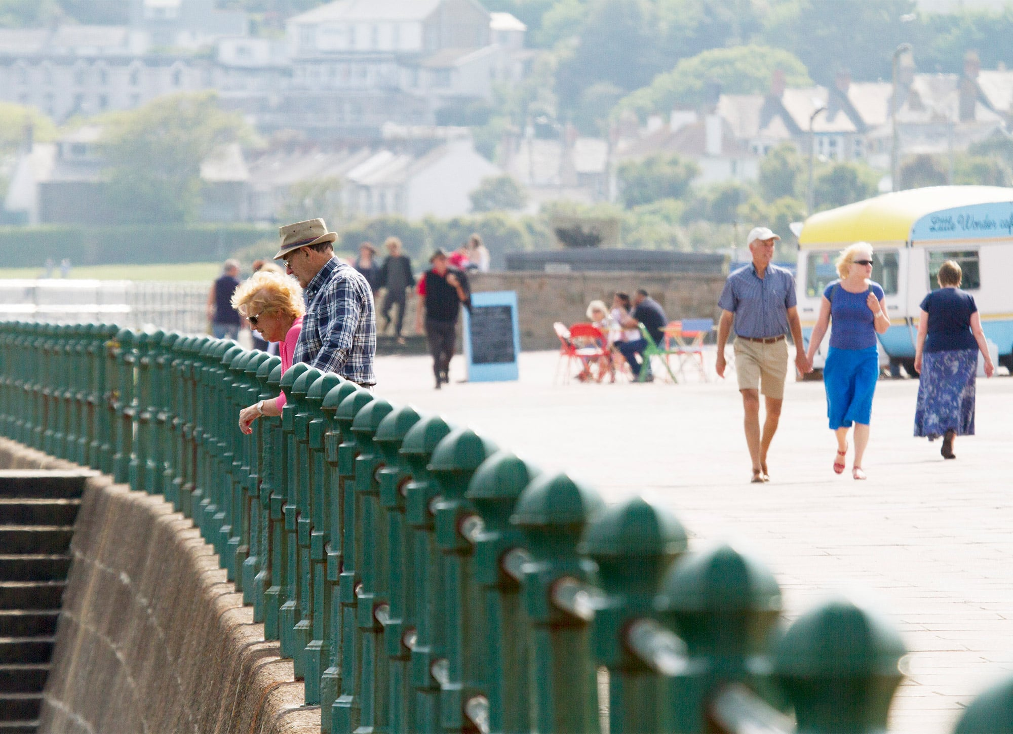 View of couple walking down the Penzance promenade with the Little Wonder cafe in the background